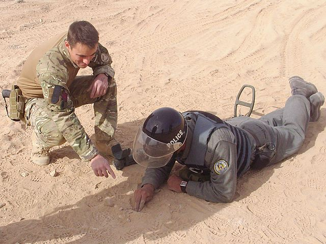 British Army mentor instructs an Afghan National Police recruit during a counter-improvised explosive device course in Helmand province