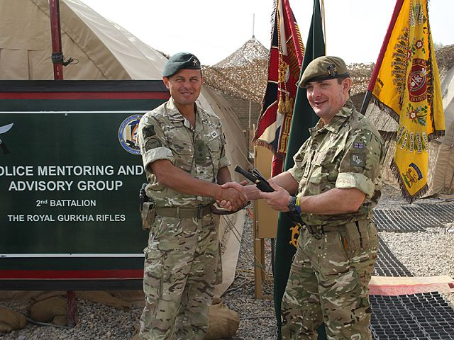 Lieutenant Colonel James Coote (right), Commanding Officer of 1st Battalion The Princess of Wales's Royal Regiment, exchanges gifts with Lieutenant Colonel Fraser Rea, Commanding Officer of 2nd Battalion The Royal Gurkha Rifles, during the handover of the Police Mentoring and Advisory Group in Lashkar Gah, Helmand province