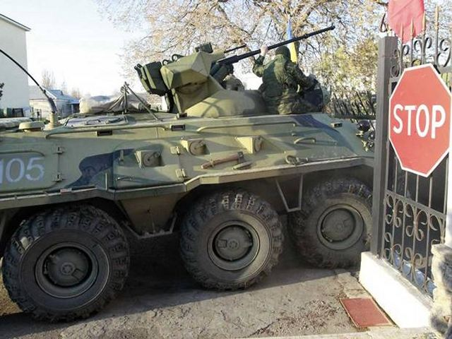 Russian troops forced their way into a Ukrainian airbase in Crimea with armored vehicles, automatic fire and stun grenades on Saturday, March 22, 2014, injuring a Ukrainian serviceman and detaining the base's commander for talks.